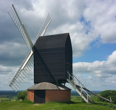 Traditional windmill with white sails, black top and brick base. There is a steep ladder of white steps leading down from the upper part of the windmill opposite the sails. There is green grass in the foreground and the sky is blue with white and pale grey clouds. It is a sunny day.