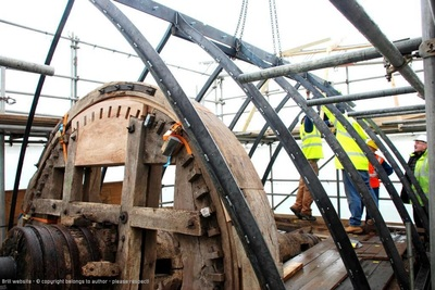 The picture is dominated by a large toothed wooden wheel standing upright. There are metal bars looping overhead and the open sky beyond. There is builder's scaffolding around the picture and two men in bright yellow hi-vis jackets standing on the right of the picture.