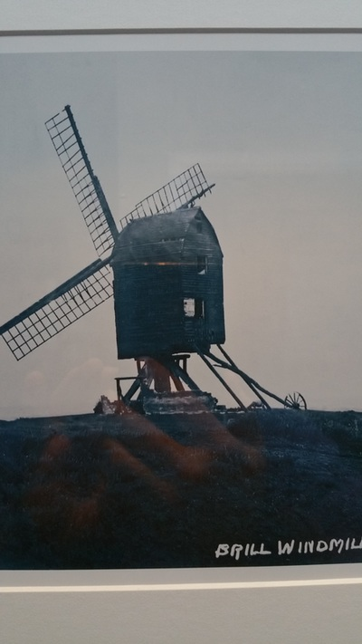 A rather indistinct photo of a traditional windmill. The base of the windmill has been removed exposing metal struts and beams of wood. The top of the windmill and the sails look tatty. The foreground is indistinct and the sky is grey.