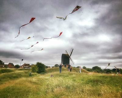 Traditional windmill in the middle distance on top of a small grassy hill. There are three or four figures close to the windmill flying kites. The sky is grey and cloudy. There are eight diamond shaped kites of various colours flying with long tails streaming out to the left.